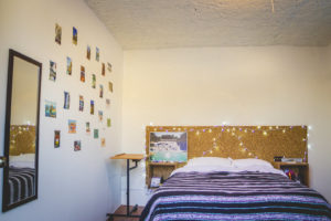 room with double bed and little lights on the back with big mirror