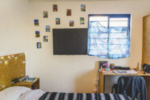 room with pictures on the wall and a desk with books