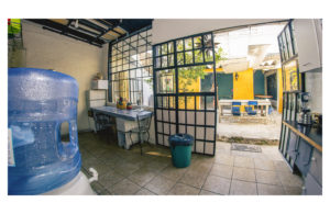 Kitchen with view to the patio doors open, there is a blender drinking water a microwave and kitchenware