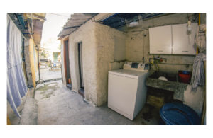 Laundry room in old house with one washing machine and a sink