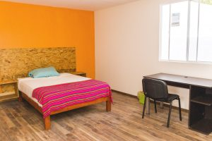 Room with double bed, yellow wall with a desk for students